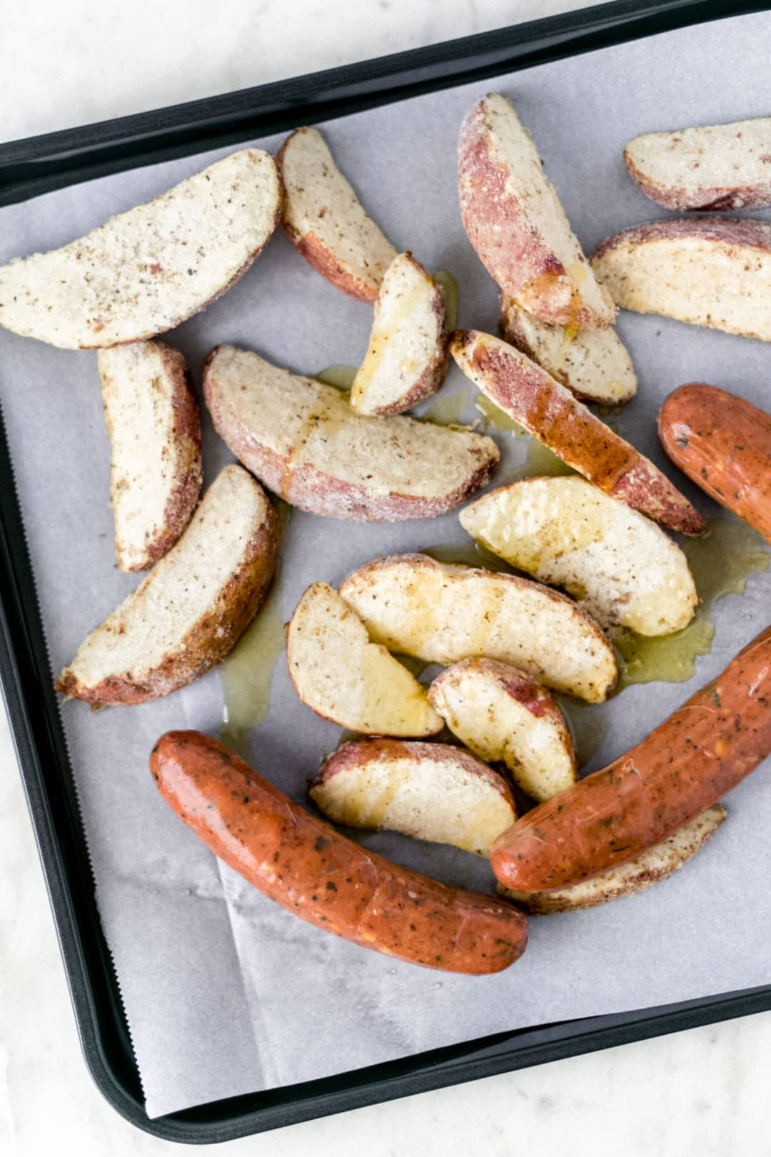 sausage, potato wedges, and olive oil on sheet pan