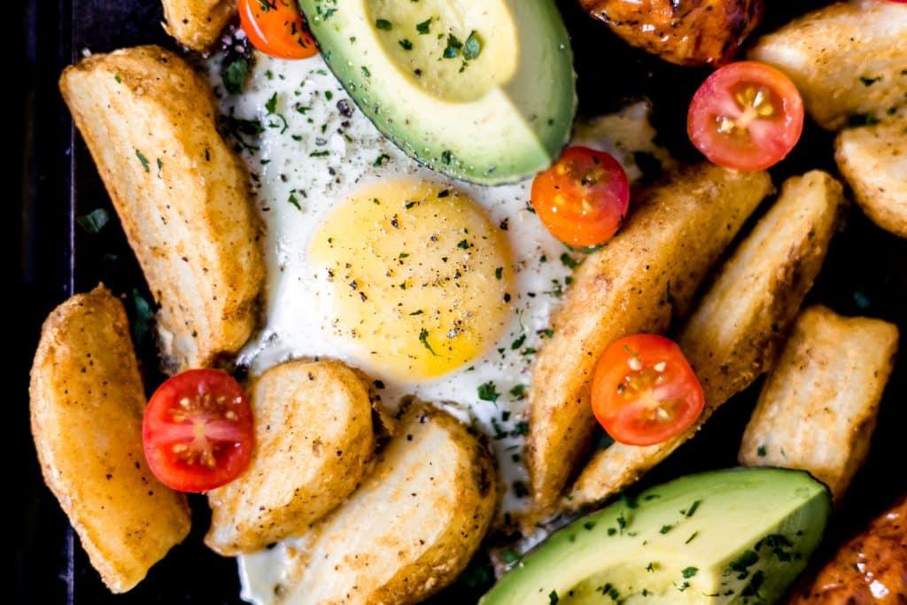 close-up photo of sheet pan breakfast bake egg, potatoes, avocado, tomatoes
