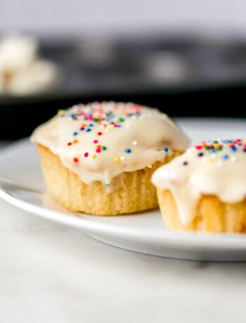 close up side view of two vanilla cupcakes on a white plate topped with sprinkles