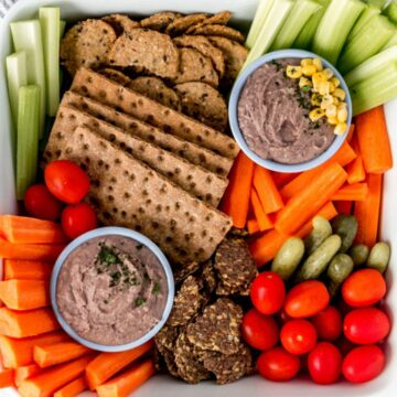 overhead view of black bean dip in a colorful vegetable platter