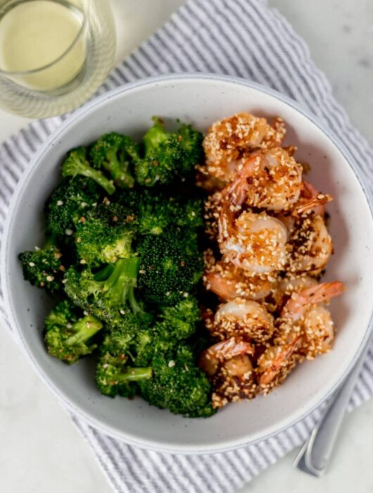 sesame shrimp in a bowl with a glass of white wine
