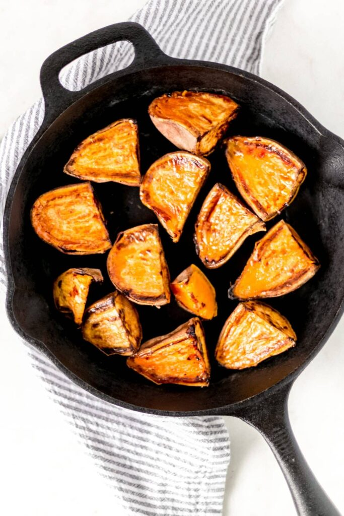 Roasted sweet potato halves in a cast iron skillet