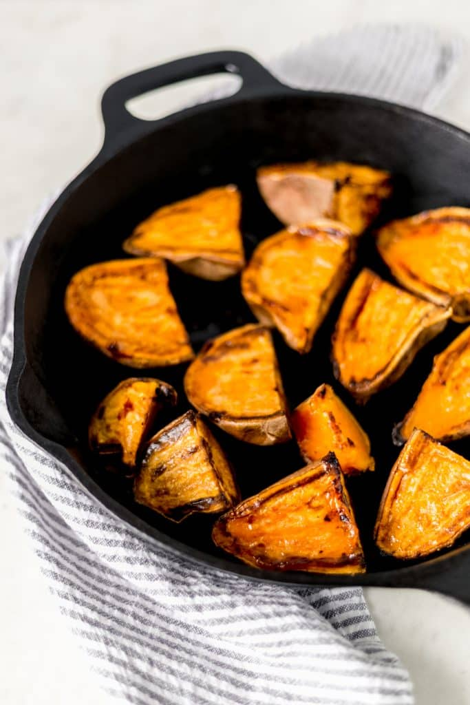 Close-up side view of oven roasted sweet potatoes in a cast iron skillet