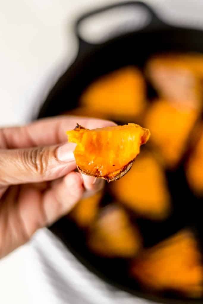 Close-up of hand holding a bite of roasted sweet potato