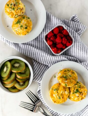 overhead view breakfast egg muffins on white plates with kiwi and raspberry