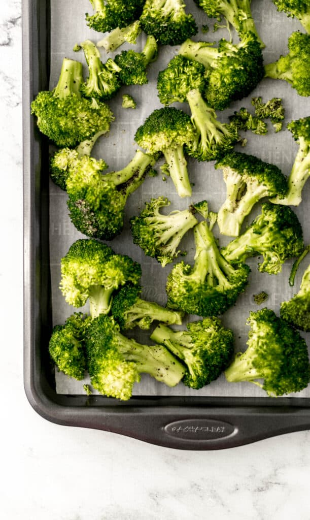 fresh broccoli on parchment lined baking sheet.