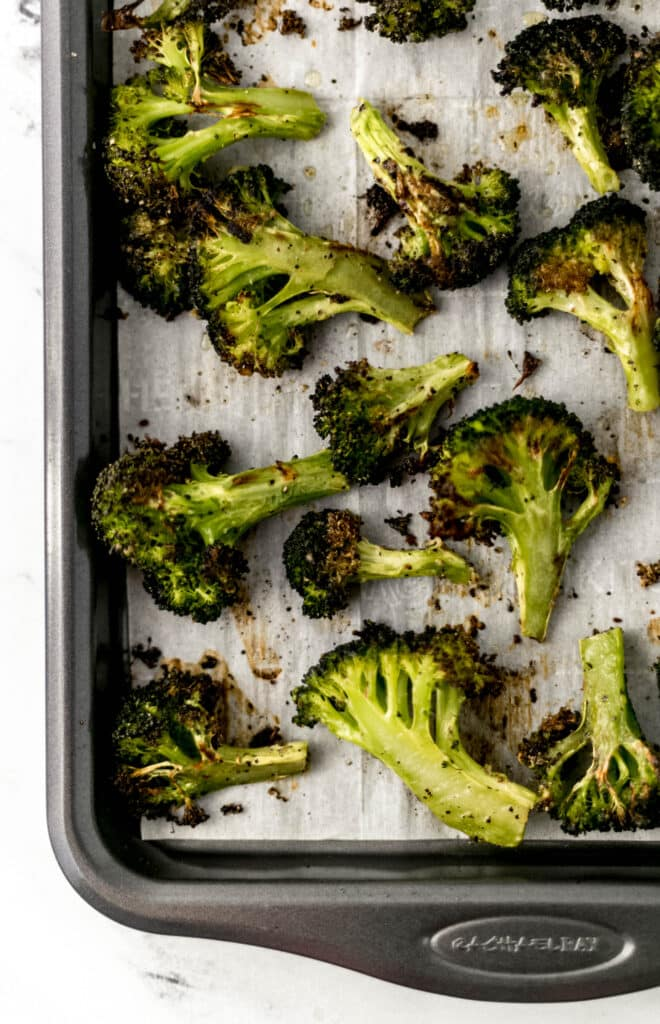 roasted broccoli on oven lined parchment baking sheet.