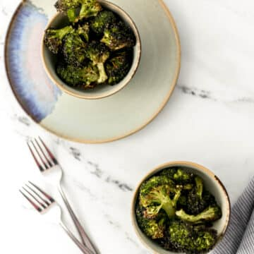 overhead shot of roasted broccoli in two small bowls on marble surface.