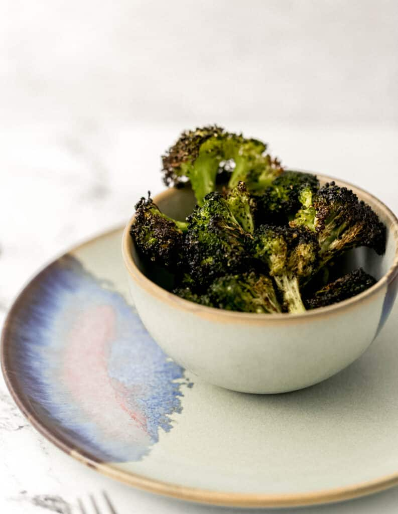close up side view baked broccoli in small bowl over small plate.
