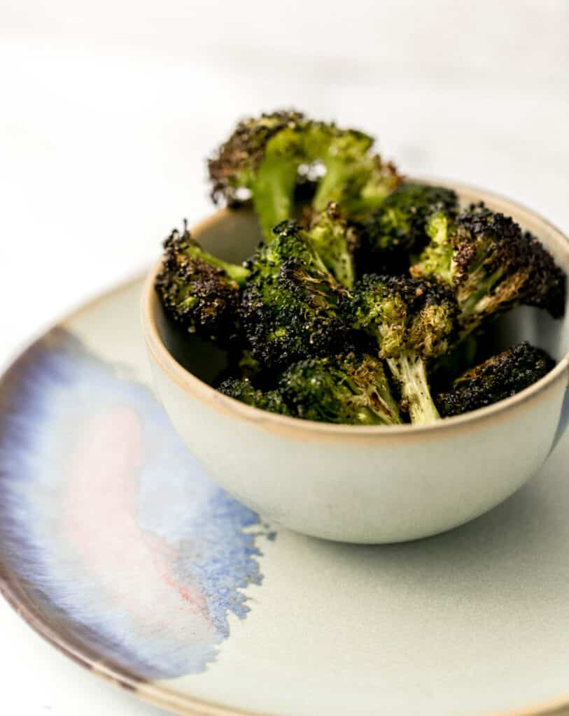 close up side view oven roasted broccoli in small serving bowl.