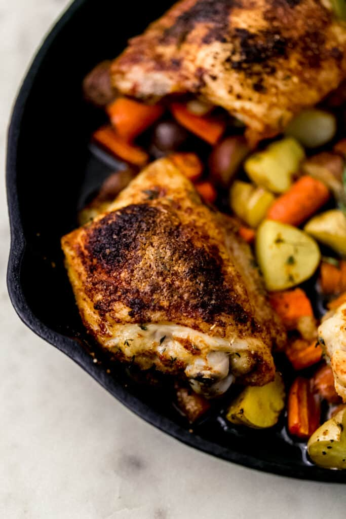 overhead view roasted chicken thighs, potatoes and carrots in cast iron skillet
