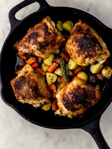 overhead view cast iron skillet with chicken, potatoes, and carrots in it on marble surface.