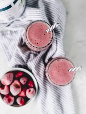 overhead view of strawberry smoothie with bowl of frozen strawberries