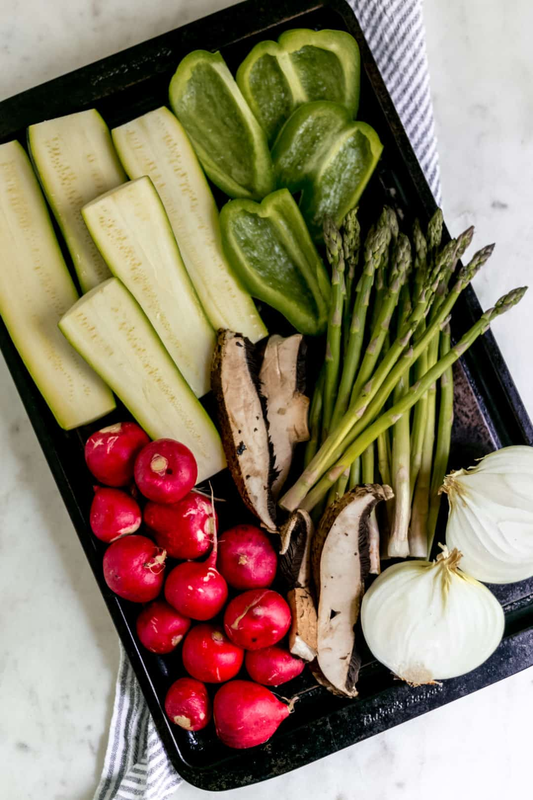 cut raw vegetables on a sheet pan over a nakpin