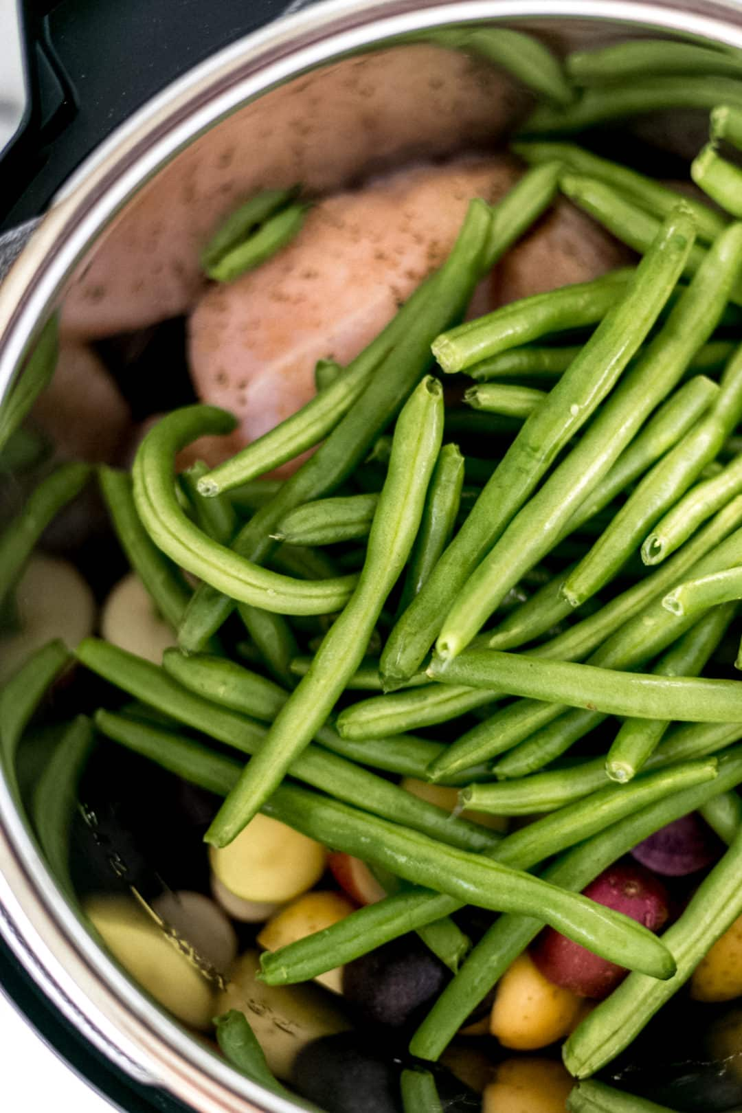 green beans on top of chicken and potatoes in an instant pot