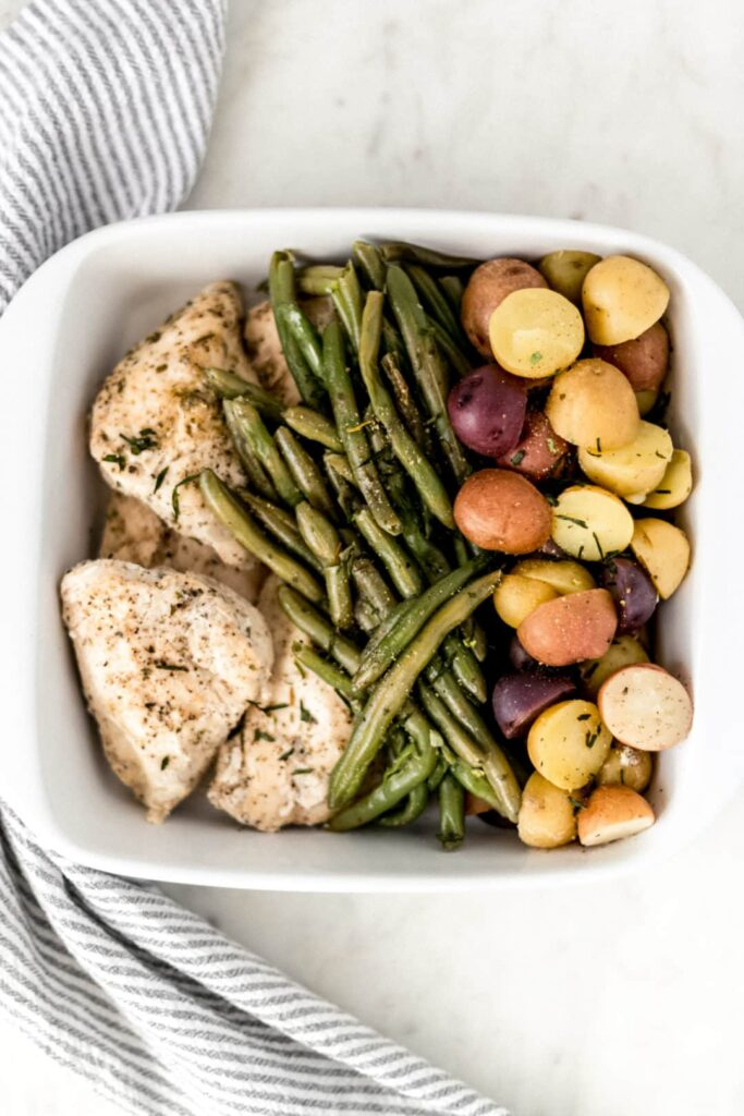white platter with chicken, potatoes, and green beans