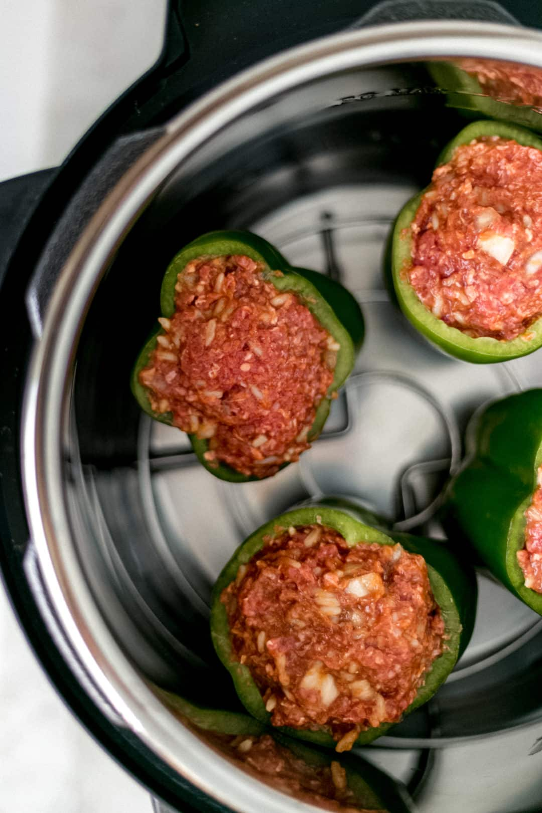 four raw stuffed peppers in an instant pot