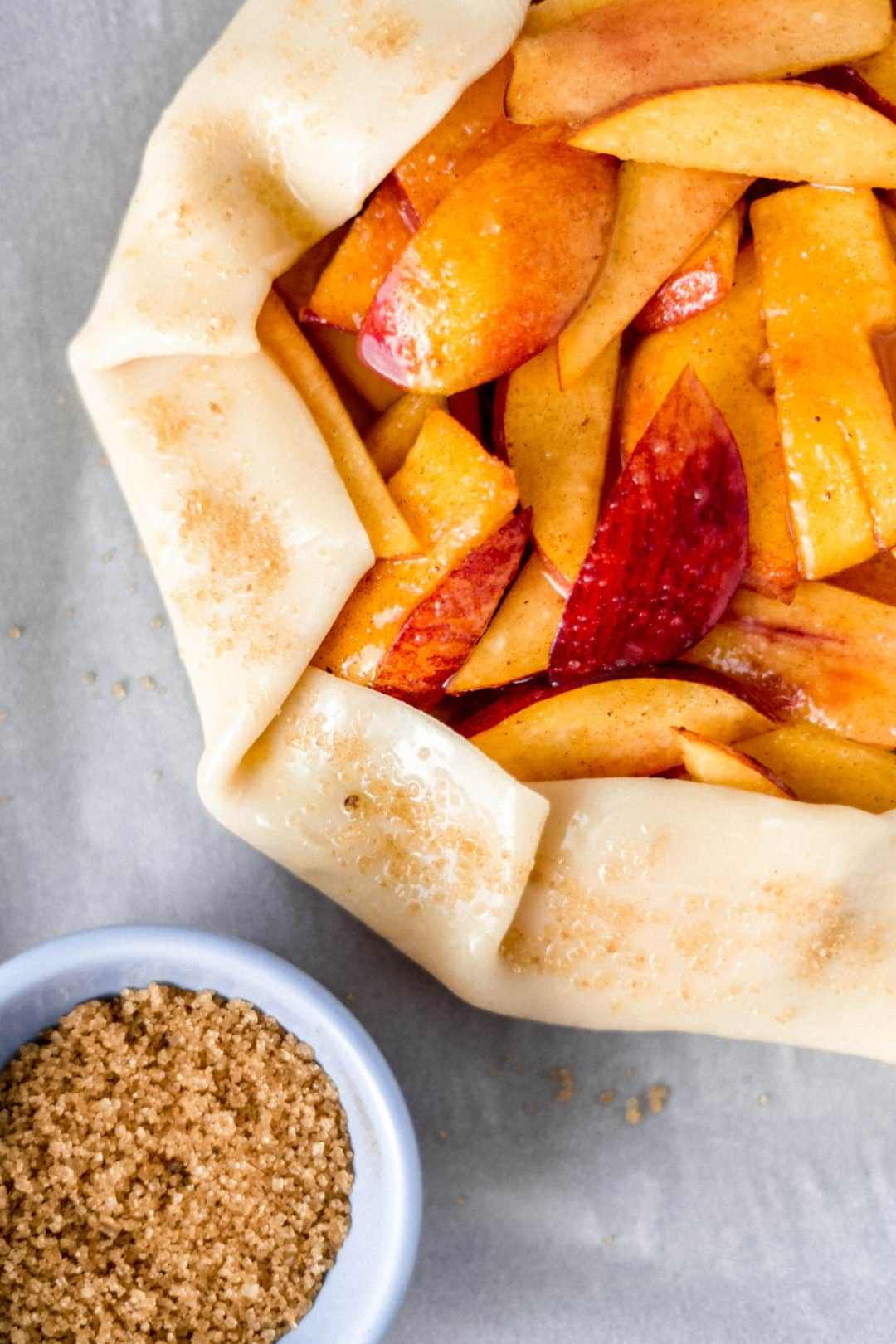 small blue bowl of raw sugar next to uncooked peach galette