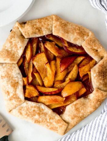overhead view peach galette with napkin, white plates, and a knife