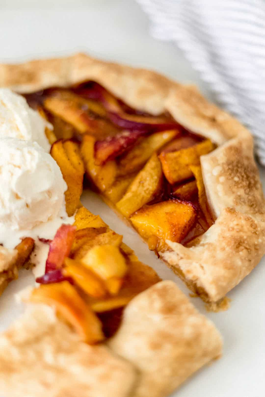 close-up side view peach galette next to a napkin and topped with vanilla ice cream