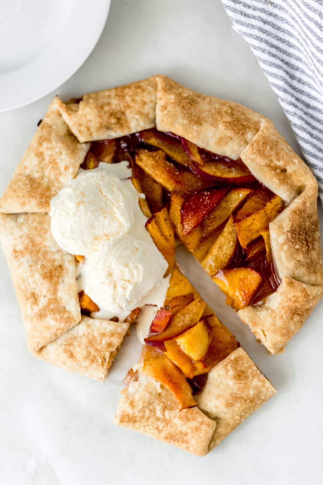 overhead view of peach galette topped with two scoops of vanilla ice cream
