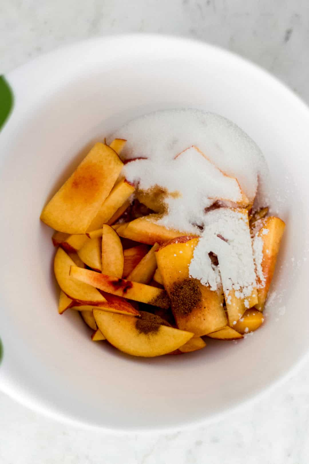 ingredients for peach galette in large white bowl with green rim