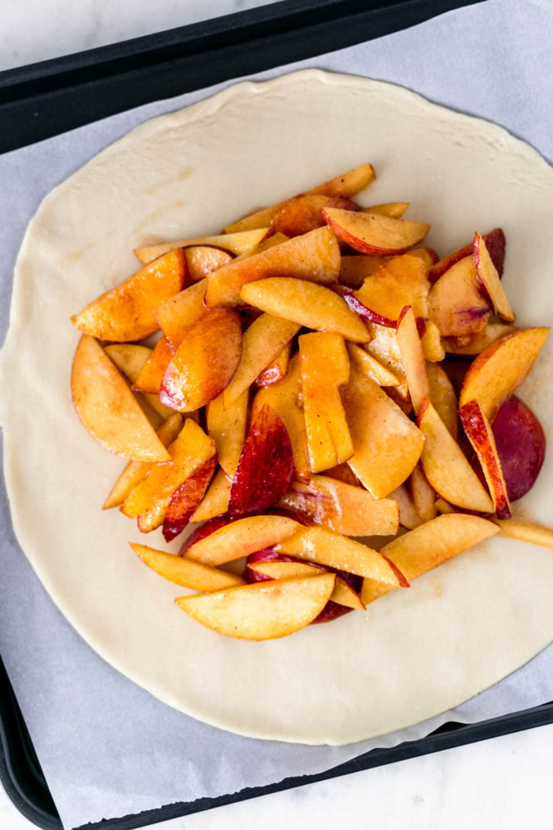 flat pie crust topped with peach mixture for peach galette