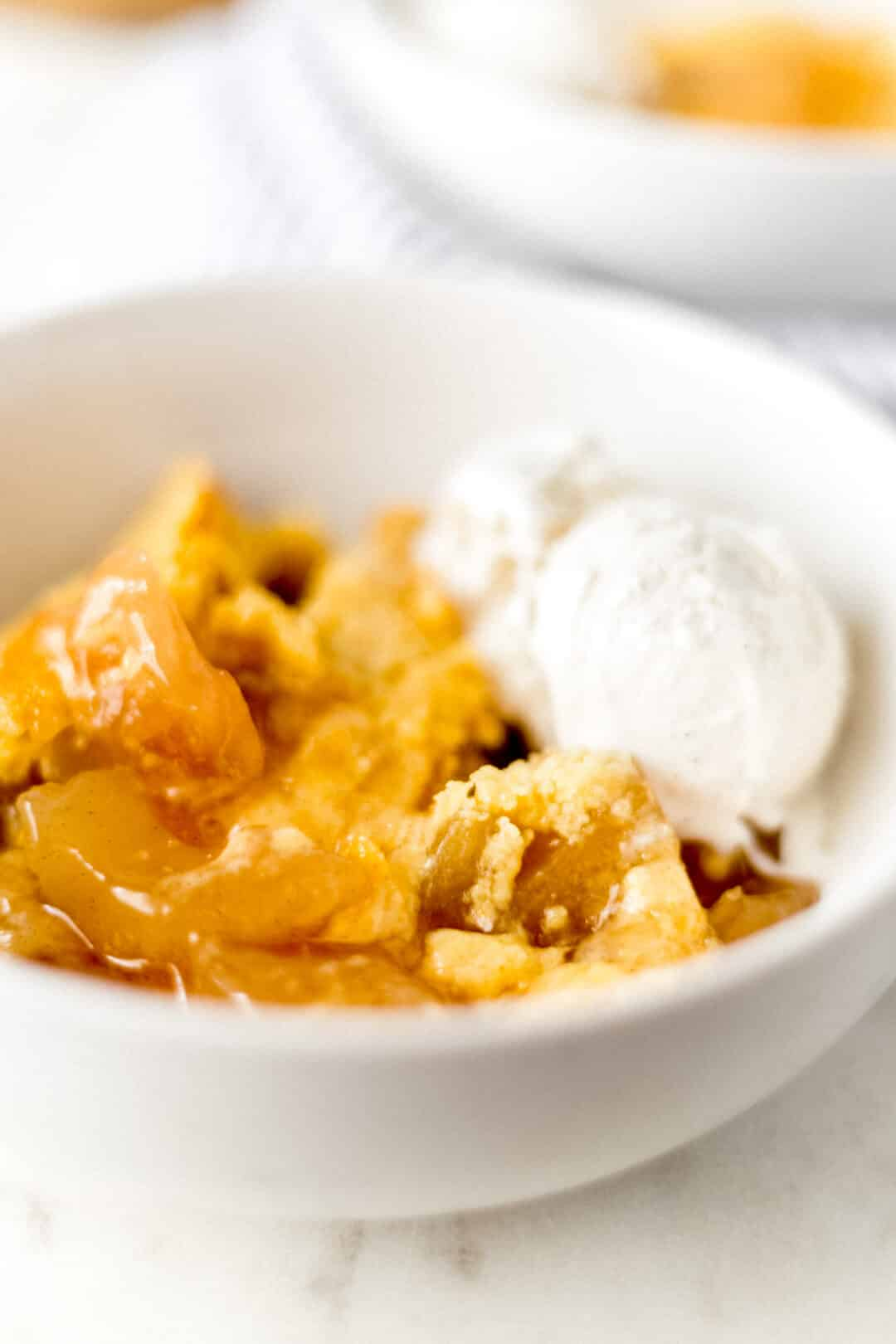 close up side view apple dump cake in white bowl