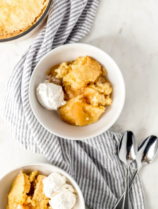 apple dump cake in white bowl with spoons and ice cream