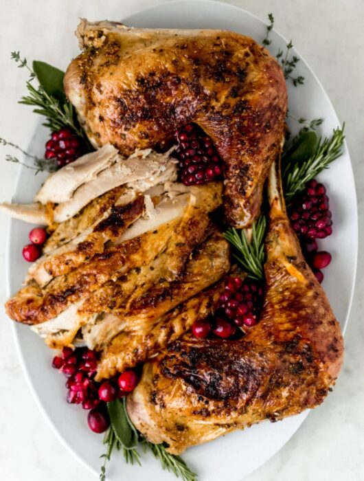 turkey arranged on white platter with fresh herbs and cranberry