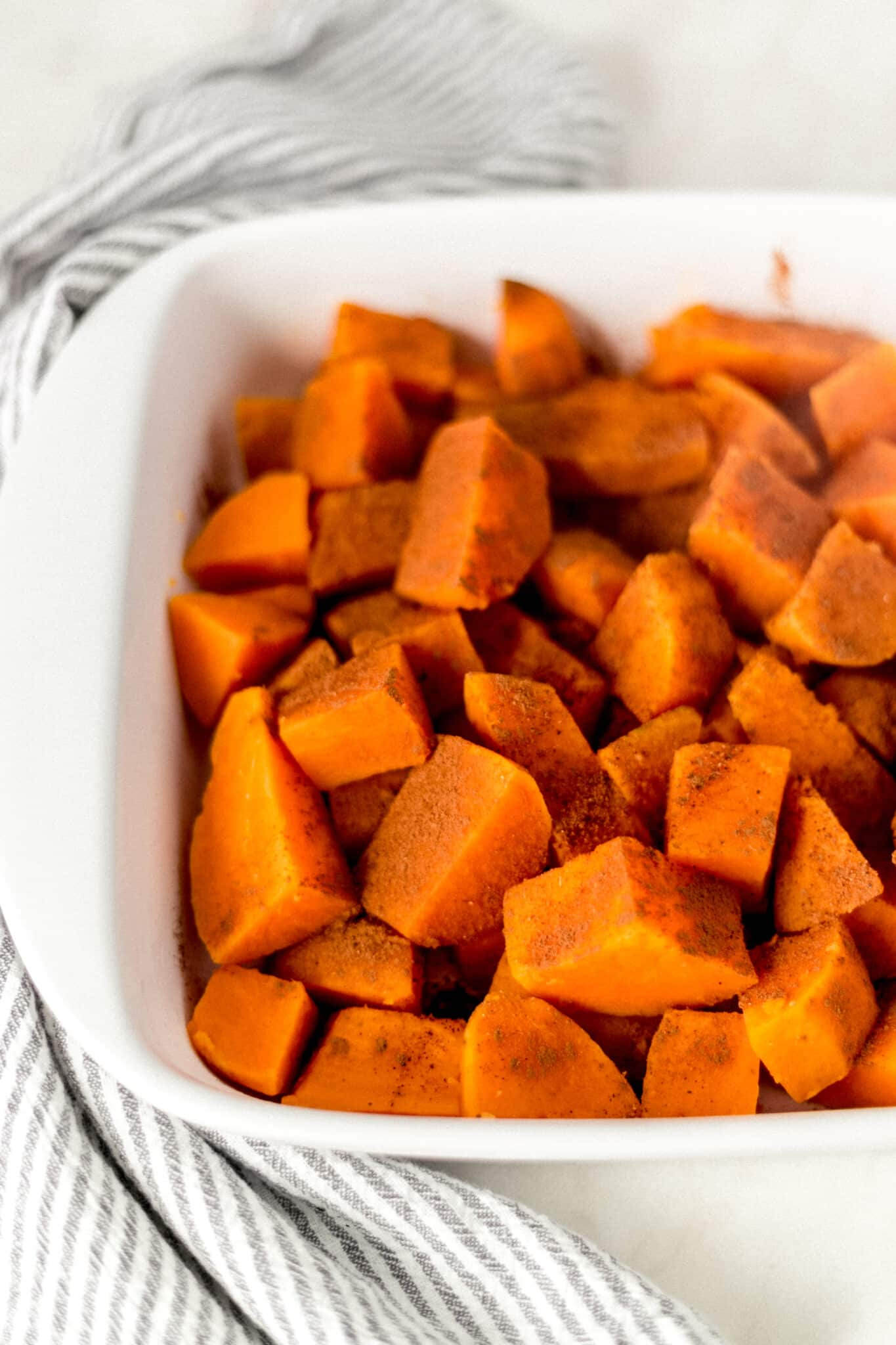 yams in a white baking dish sprinkled with cinnamon and nutmeg