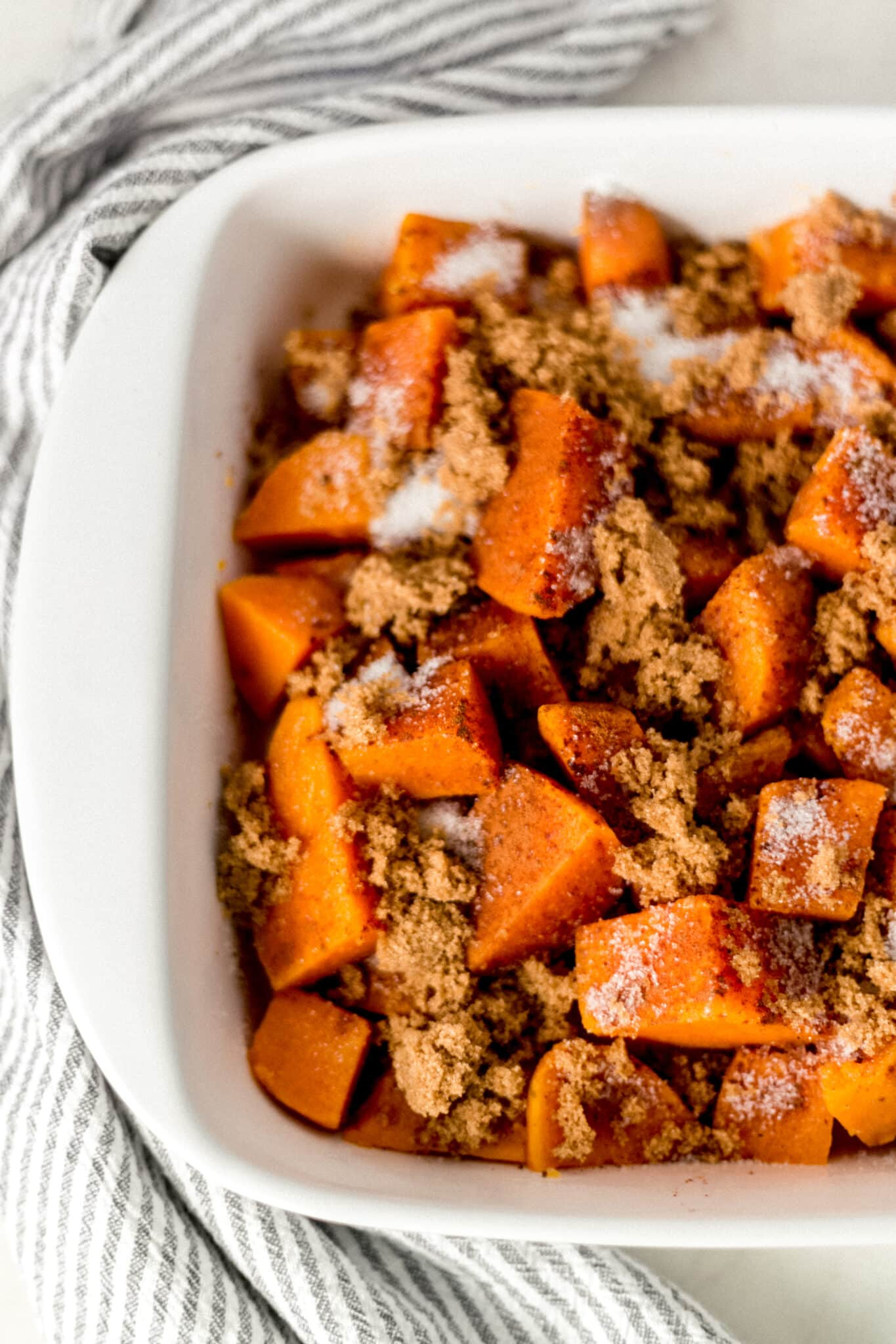 yams in a white baking dish topped with granulated sugar and brown sugar