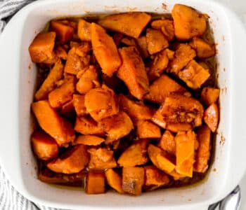 easy candied yams in a white serving dish over a napkin with two spoons