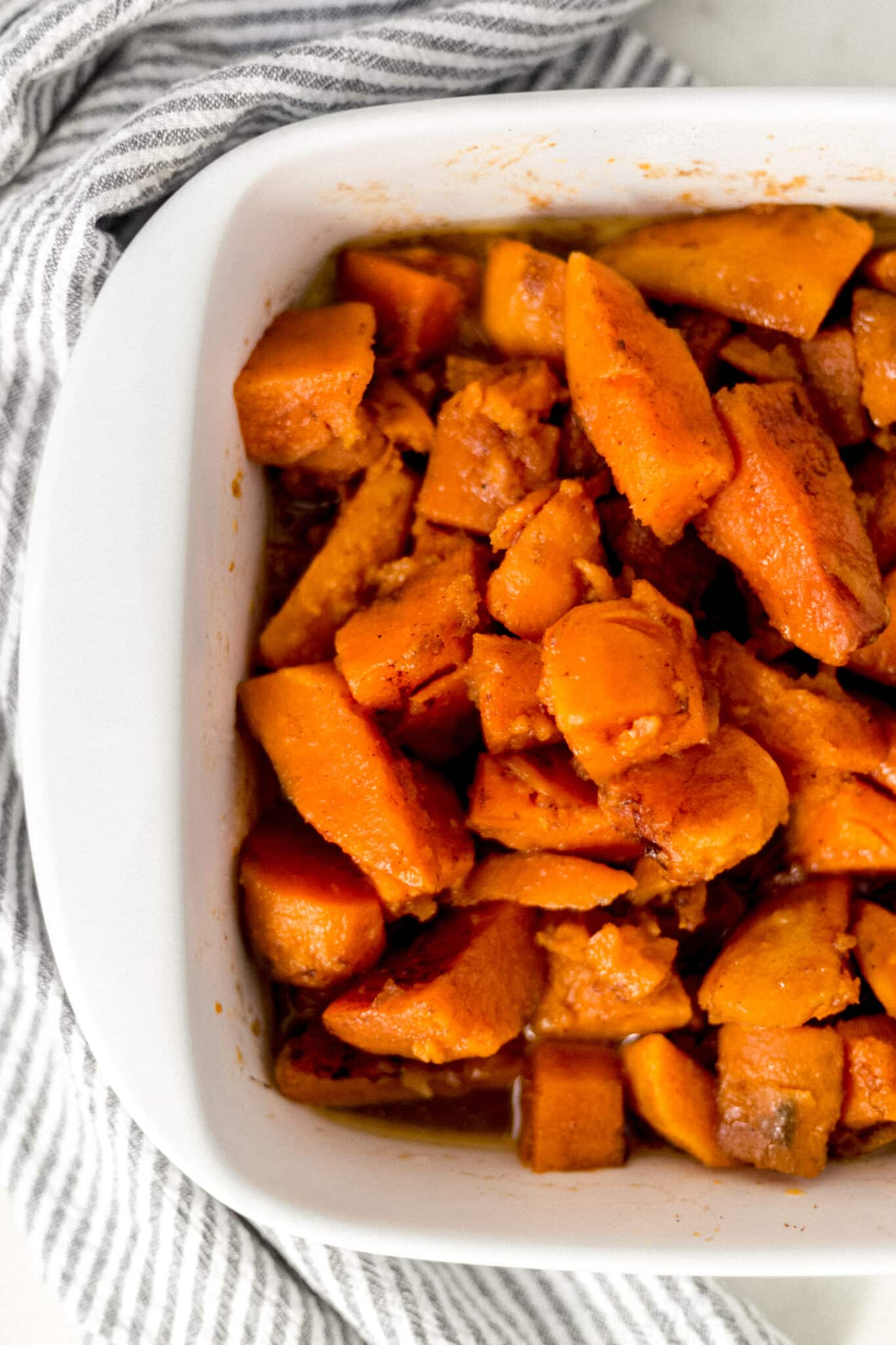 dish with baked candied yams next to a striped napkin