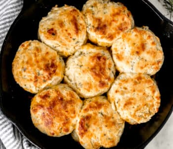 overhead view cheddar herb biscuits in cast iron skillet with napkin and fresh herbs