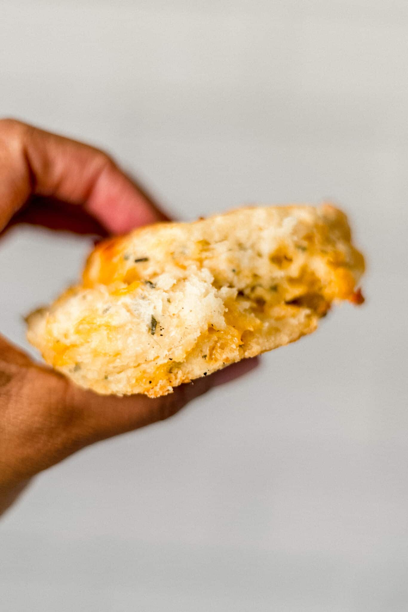 close up side view of hand holding cheddar herb biscuit