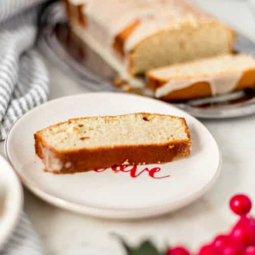 side view of slice of eggnog pound cake on plate with full cake in the background