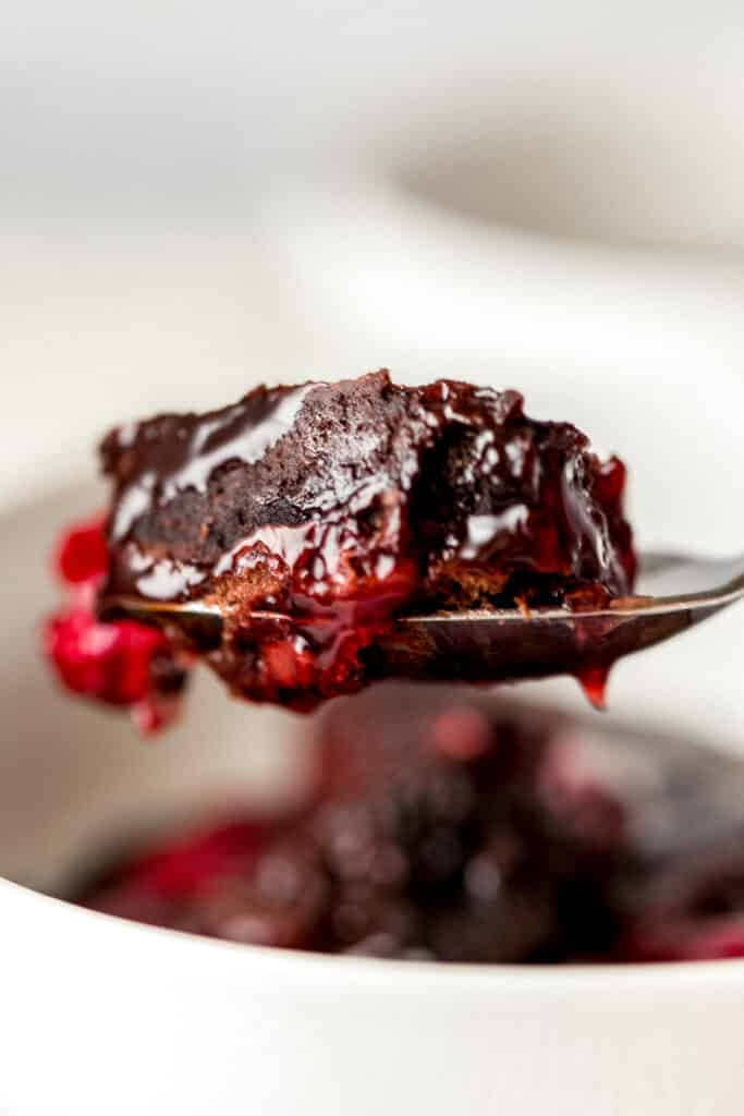 instant pot chocolate cherry dump cake on spoon being held by hand