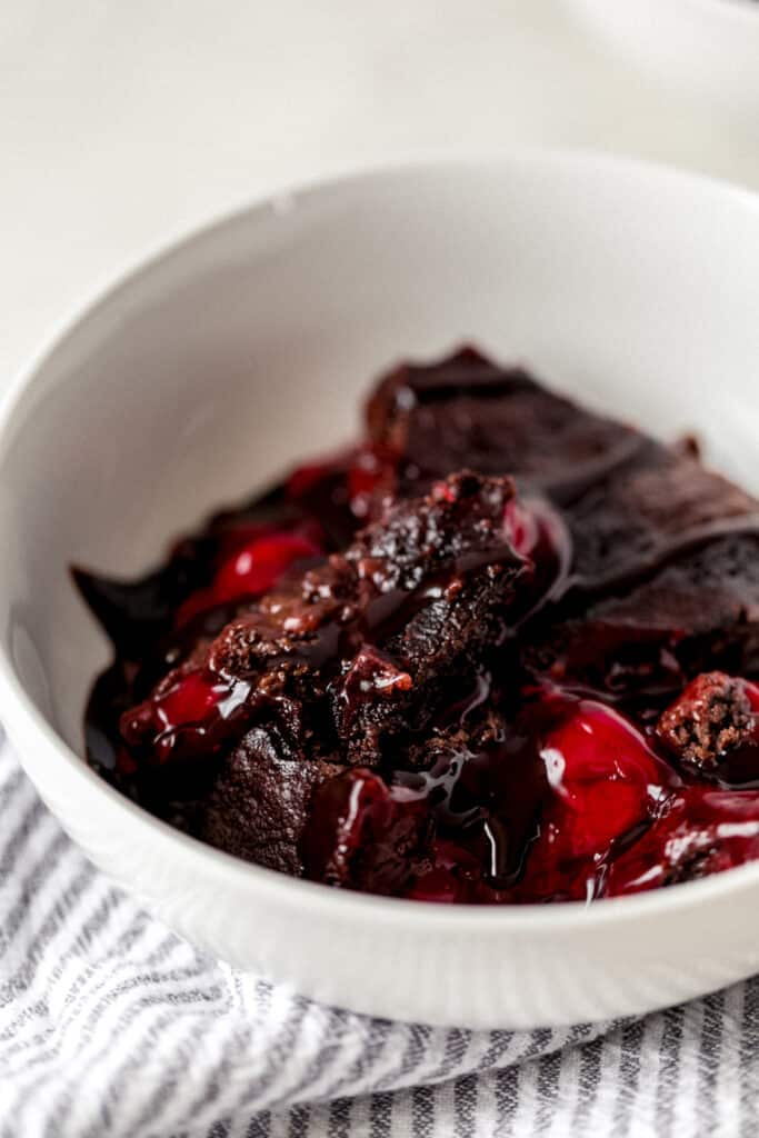 side view chocolate cherry dump cake serving in white bowl with napkin