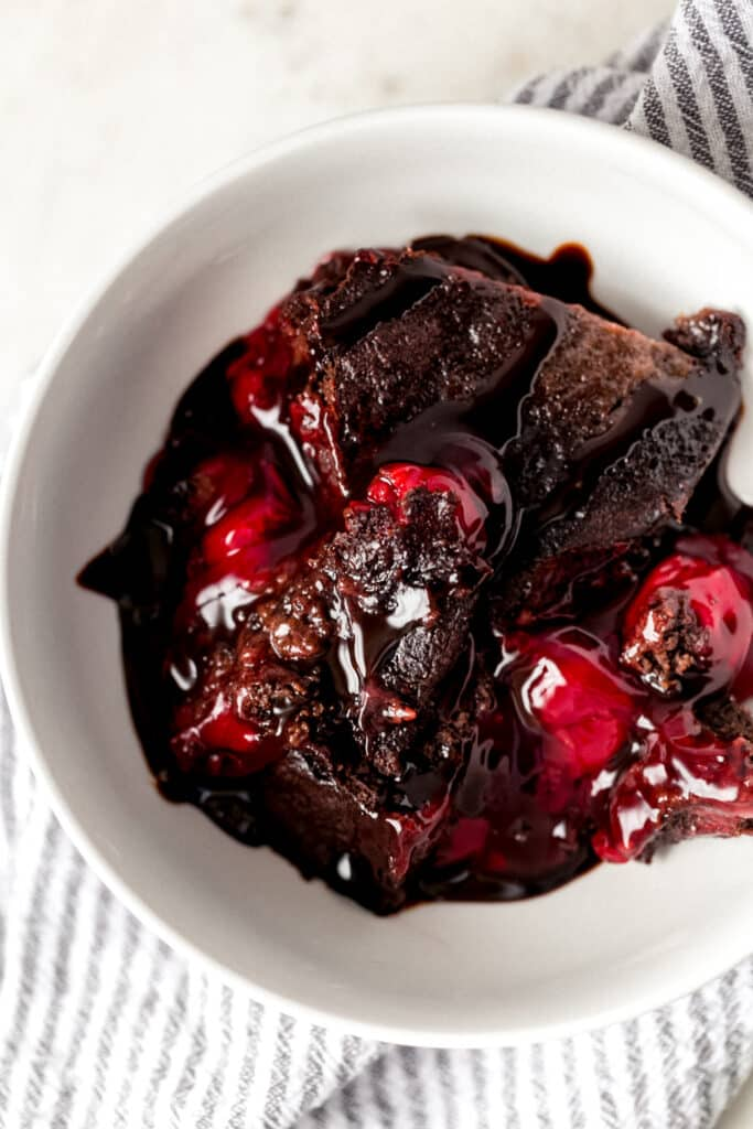 overhead view instant pot chocolate cherry dump cake in small white bowl with napkin