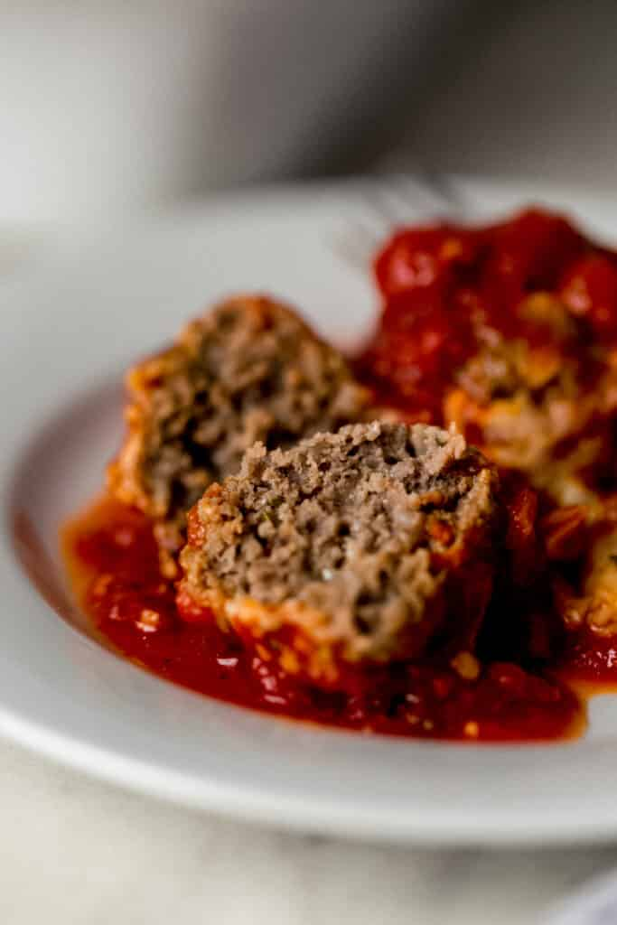 two meatballs from keto meatball casserole on small white plate.