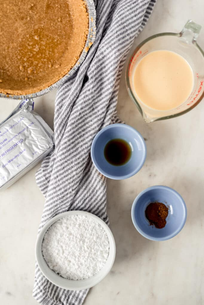 ingredients for no bake eggnog cheesecake in small bowls and containers with napkin