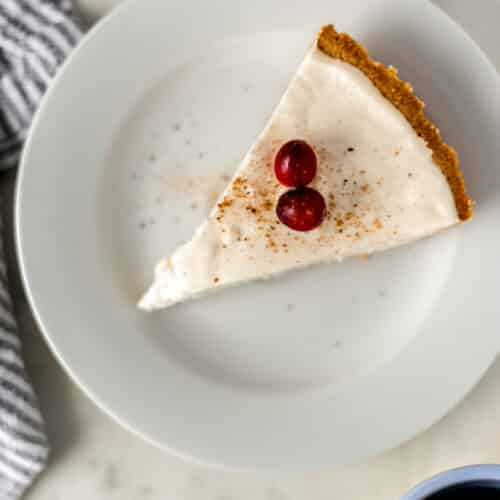 overhead view piece no bake eggnog cheesecake on small white plate