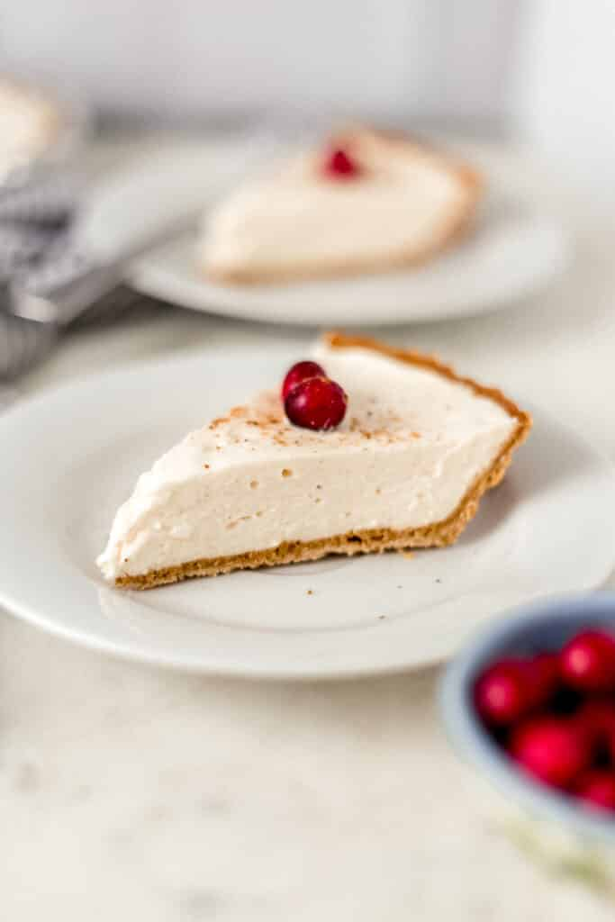 slice of eggnog cheesecake on a white plate with another slice in the background