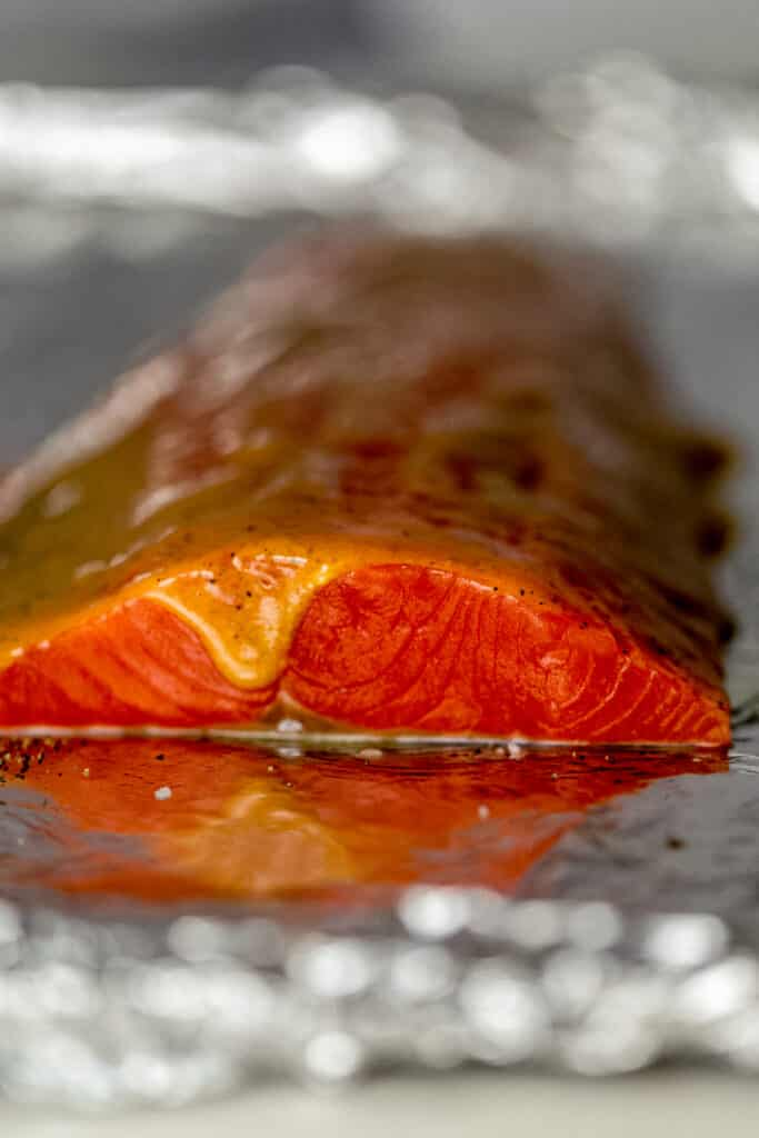 side view salmon on foil lined sheet pan topped with brown sugar Dijon mustard glaze