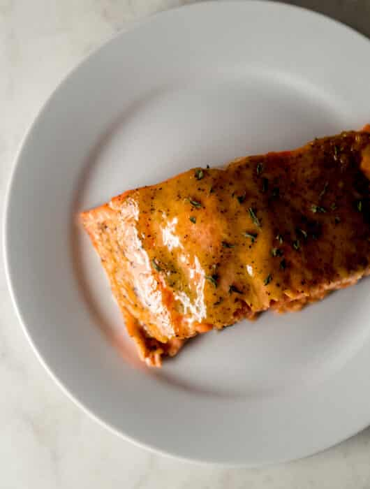 overhead view piece of brown sugar dijon glazed salmon on white plate