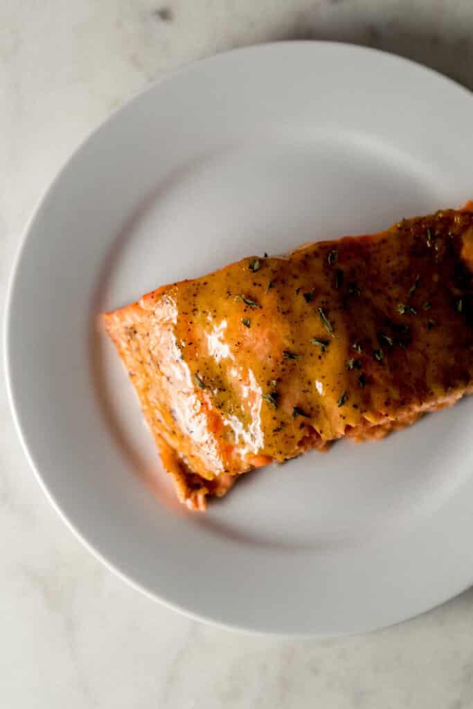 overhead view piece of brown sugar dijon glazed salmon on white plate