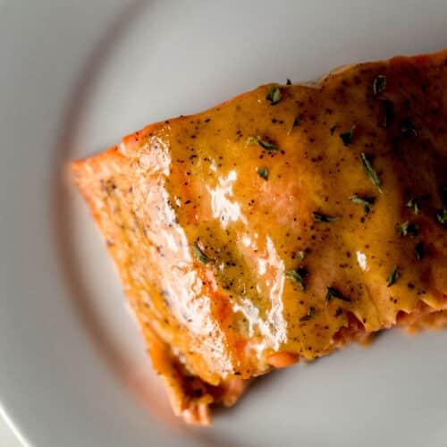 piece of brown sugar dijon glazed salmon on white plate