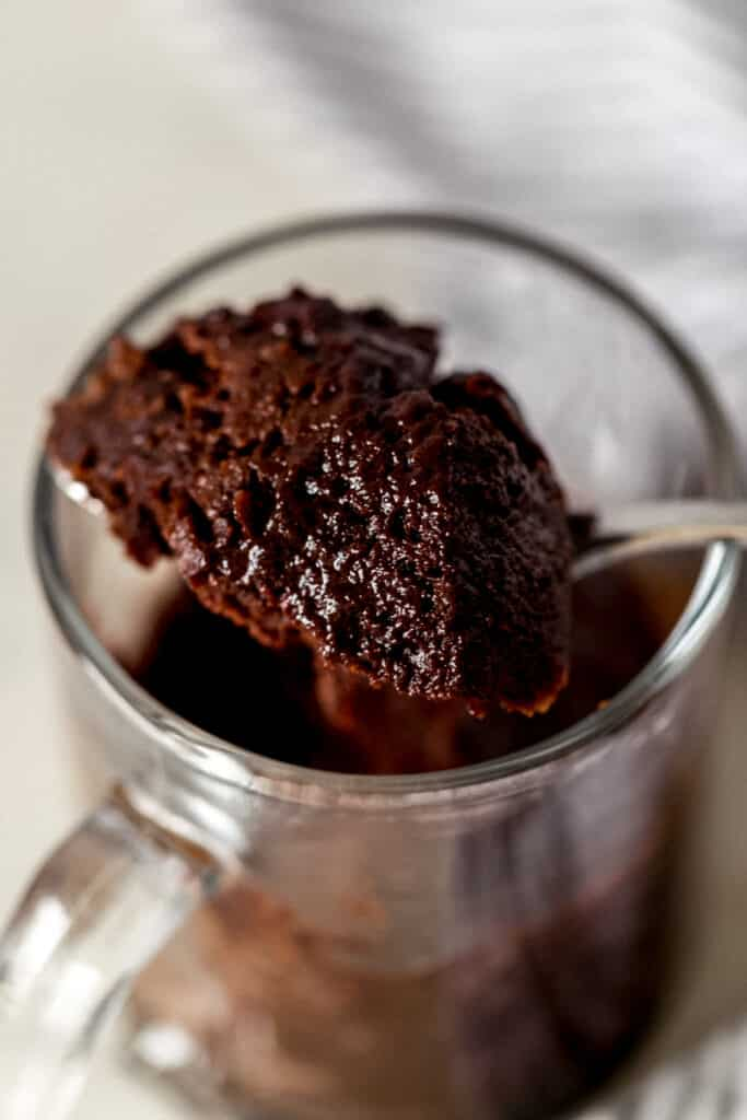 hand holding spoon with some microwave mug brownie on it