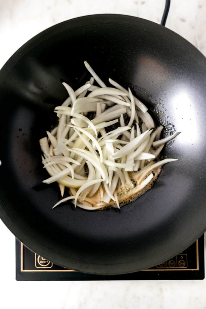 sliced onion in a wok with cooking oil and butter